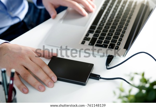 External backup disk hard drive connected to laptop. Man with notebook making safety personal data copy.
