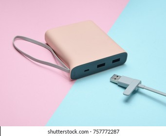 External battery for charging smartphones and gadgets with a usb cable close-up on a pink blue pastel background. Power bank. Modern technologies.