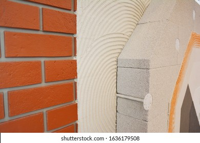 External brick wall insulation. House brick wall insualtion with glue plastering layers,  reinforcment mesh, aerated concrete blocks, finishing render.