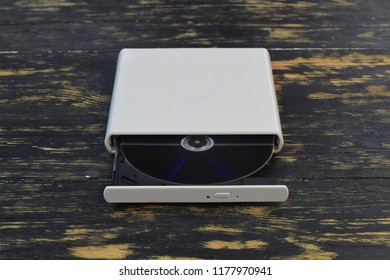 External CD/DVD/Blu-Ray Drive with opened tray and gray Blu-ray (BD) disc on dark brown background (front angle view)