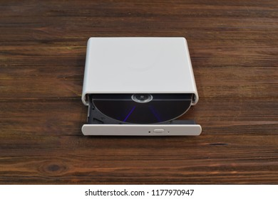 External CD/DVD/Blu-Ray Drive with opened tray and gray Blu-ray (BD) disc on light brown background (front angle view)