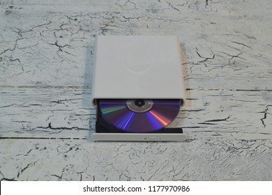 External CD/DVD/Blu-Ray Drive with opened tray and purple Blu-ray (BD) disc on white wooden background (front angle view)