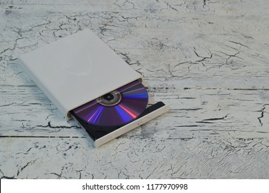 External CD/DVD/Blu-Ray Drive with opened tray and purple Blu-ray (BD) disc on white wooden background (left angle view)