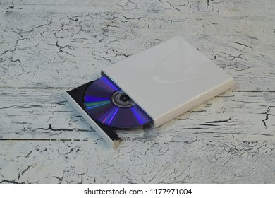 External CD/DVD/Blu-Ray Drive with opened tray and purple Blu-ray (BD) disc on white wooden background (right angle view)