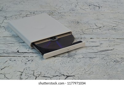 External CD/DVD/Blu-Ray Drive with opened tray and golden Blu-ray (BD) disc on white wooden background (left angle view)