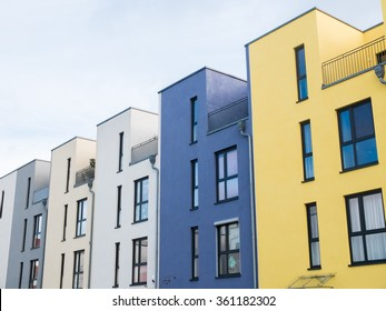 External facade of a row of colorful modern urban townhouses in yellow blue, beige and white