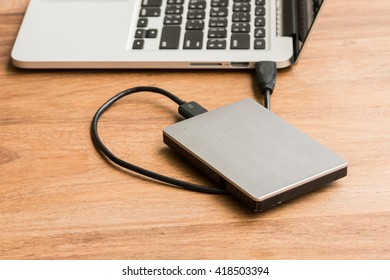 External hard drive connect to laptop computer on wooden background