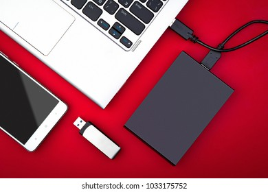 External hard drive connected to the laptop, USB flash drive and smartphone on a red background, flat lay. The concept of mobile technology