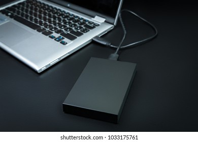 An external hard drive  connected to the laptop with a usb cable on a black background. Portable storage technologies