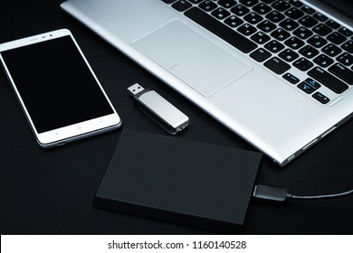 External hard drive connected to the laptop, USB flash drive and smartphone on a black background. The concept of mobile technology