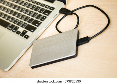 External hard drive connected to laptop computer, with selective focus
