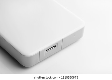 External hard drive of white color on a white background. Information base. Additional memory. Data storage. Repair of computer equipment. Closeup.