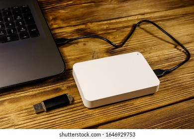 External HDD connected to laptop computer and USB flash drive on a wooden desk. Concept of data storage