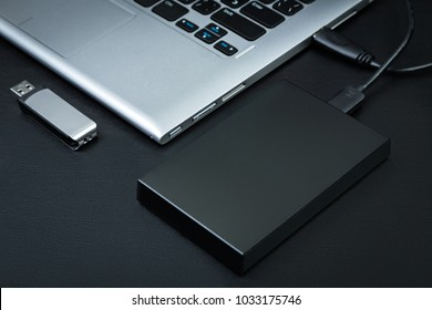 External hdd connected to the laptop and USB flash drive on a black background, top view. The concept of portable data storage