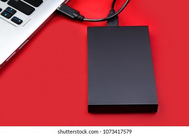 An external hdd connected to the laptop with a usb cable on a red table. Portable storage technologies