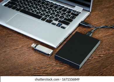 An external hdd connected to the laptop with a usb cable on a brown table. Portable storage technologies