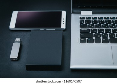 External hdd with the laptop, USB flash drive and smartphone on a black background. The concept of portable business technology