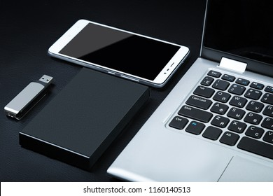 External hdd with the laptop, USB flash drive and smartphone on a black background. The concept of portable data storage