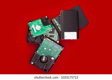 External and internal hard drives in a pile on the board. Computer storage concept.