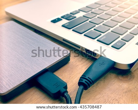 External or portable hard drive (HDD) connected to laptop computer for transfer or backup data on wooden texture office desktop