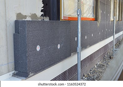External thermal insulation of a building on a construction site with styrofoam sheets.