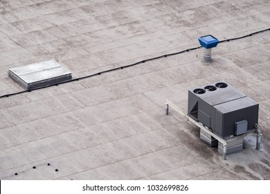The external units of the commercial air conditioning and ventilation systems are installed on the roof of an industrial building.