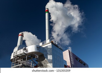 External view of the modern biomass co-generation power plant with two smoking chimneys on the beautiful blue sky background