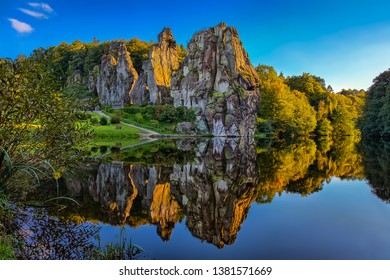 The Externsteine in the evening at sunset with the lake in the foreground and beautiful reflections in the water.