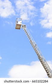 Extinct firefighter ladder with blue sky and clouds. White rescue ladder