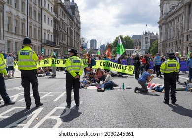 Extinction Rebellion protest down Whitehall in protest against HMRC and Barclays. Protestors with arms locked in tubes surrounded by the police. London - 24th August 2021