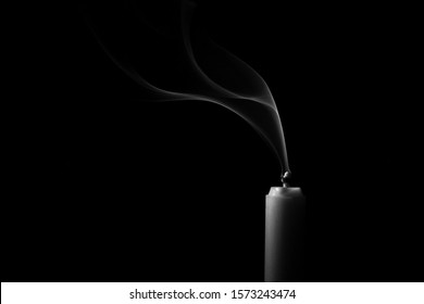Extinguished candle with a little smoke against a dark black background reflects sorrow and loneliness