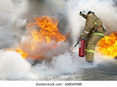 Extinguishing a major fire. A professional fireman in a special suit extinguishes an open fire with a fire extinguisher.