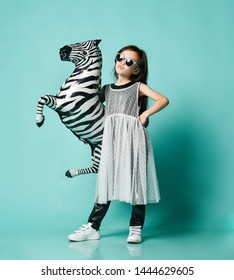 Extra cool asian baby girl kid in high fashion luxury dress and sunglasses poses with zebra metallic balloon and makes a kissy face on blue mint background