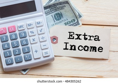 Extra Income Words on tag with dollar note and calculator on wood backgroud,Finance Concept