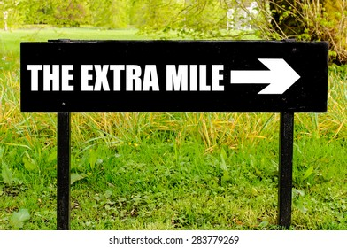 THE EXTRA MILE written on directional black metal sign with arrow pointing to the right against natural green background. Concept image with available copy space