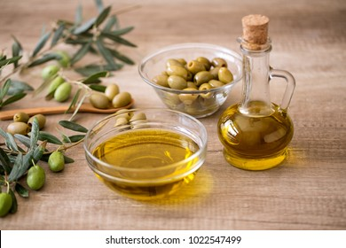 Extra virgin healthy Olive oil with fresh olive on wooden background