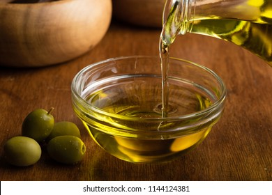 Extra virgin olive oil flowing from it's bottle
