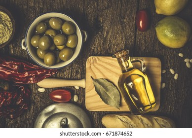 Extra virgin olive oil, green olives and food ingredients on old wooden table.