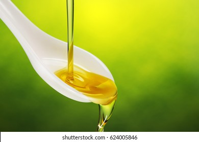 extra virgin olive oil poured in a spoon overflowing on green background