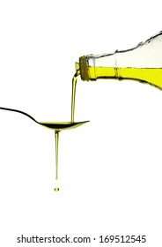 Extra virgin olive oil pouring over a spoon isolated on white with a clipping path
