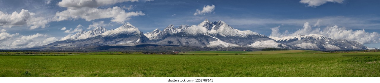 Extra wide panorama of High Tatra mountains during April with snowy hills,  blue sky with clouds, Vysoke Tatry, Slovakia