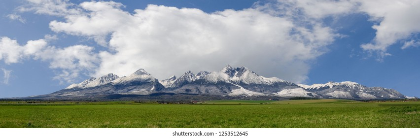 Extra wide panorama of High Tatra main ridge of mountains during April with snowy hills and blue sky with clouds, Vysoke Tatry, Slovakia