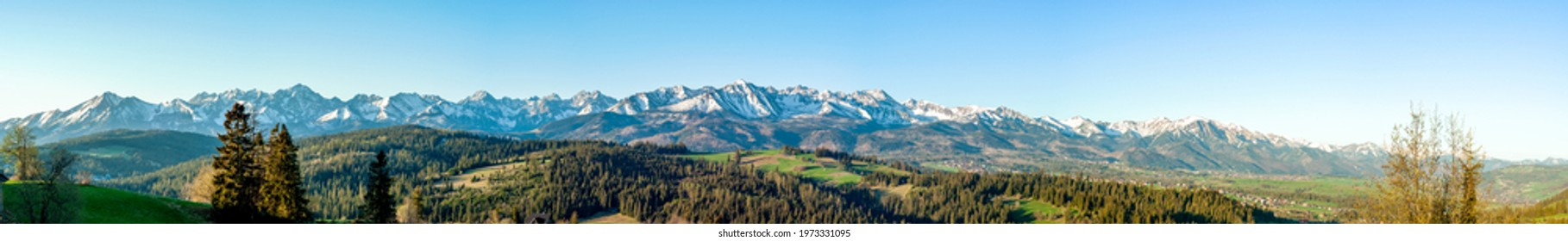Extra wide panorama of the Tatra Mountains with trees, forests and meadows in Podhale region in Poland. Early morning in spring, sunrise light