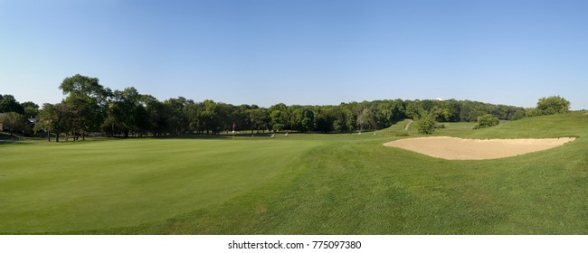 Extra wide view of a golf course featuring greens and sand trap.