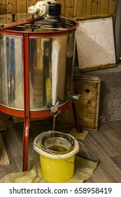 extracting honey, honey flowing out of centrifuge into a sieve hanging in a bucket