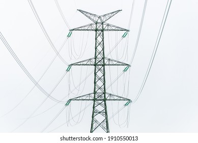 Extra-high voltage 400 kV overhead power line on large pylons, used for long distance, very high power transmission. Cloudy sky and copy space