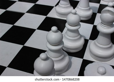 Extra-large size white chess pieces in an already started outdoor game
