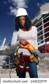 An extraordinarily beautiful young black woman wearing a tool belt that holds her dress shoes, standing in front of a demolished commercial building.