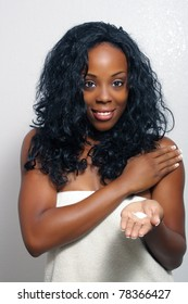 An extraordinarily beautiful young black woman with a captivating smile, wrapped in a bath towel, applies body lotion from a small amount in her hand.