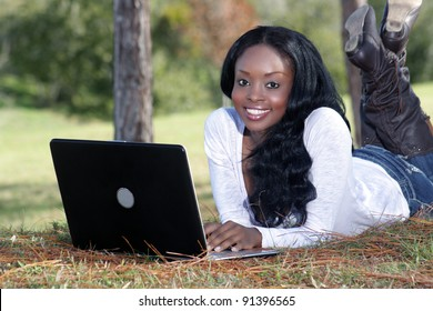 An extraordinarily beautiful young woman with a captivating smile, dressed in casual wear, works on her laptop computer outdoors.